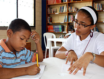 A young boy works on an assignment at a Children International community center library in Colombia.