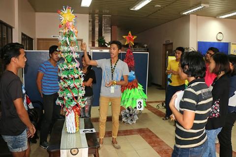 Un joven presenta su obra de arte hecha de materiales reciclados a los jueces.