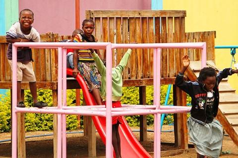 Niños africanos se divierten en un patio de recreo al aire libre