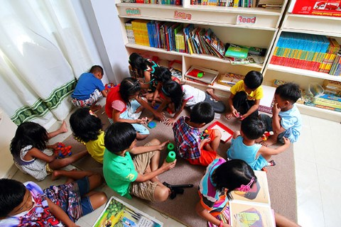 A group of kids gather for games and reading in a Philippines community center