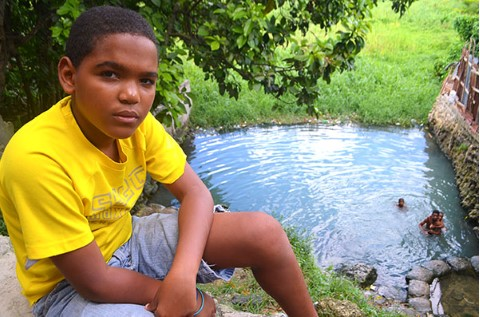 Children in poverty swim in a dangerous water well.