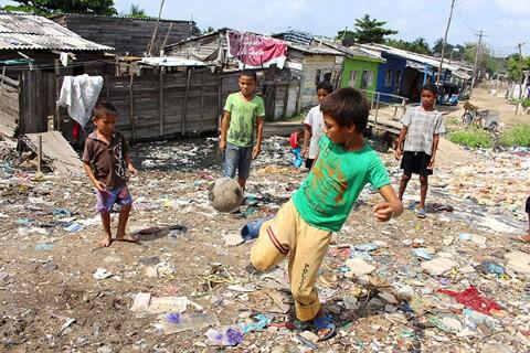 Boys kick a soccer ball among garbage