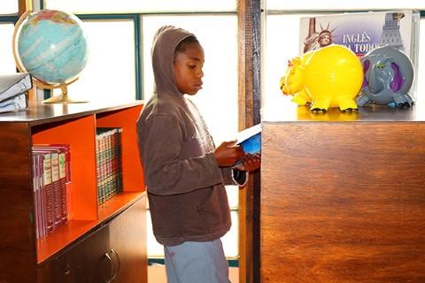 Ecuador boy reads book in CI community center library