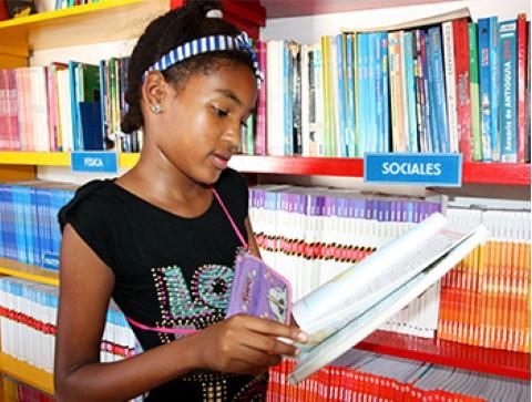 Una niña lee en la biblioteca de un centro comunitario en Cartagena, Colombia.