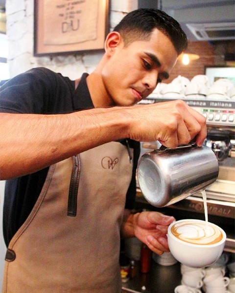Melvin shows off the cappuccino he made at work