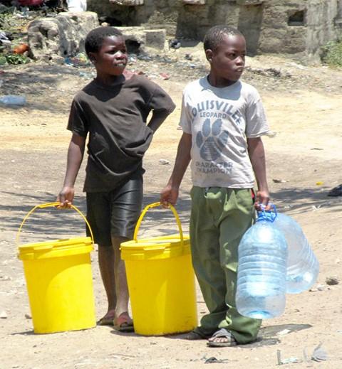 Dos niños en Lusaka caminan largos trechos en busca de agua