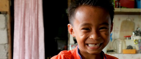 A young boy's smile reveals a missing front tooth