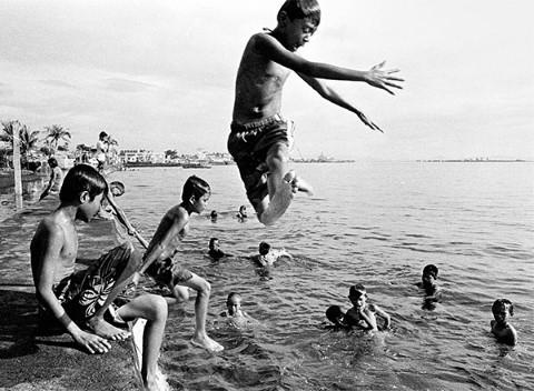 Entre la muchedumbre de nadadores, un niño salta en el océano.