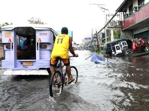 Filipinos like this man on a bike are adept at getting around during floods.