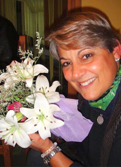 Longtime child sponsor Marily Reyes holding flowers