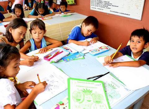 Kids at community center color nutrition workbook
