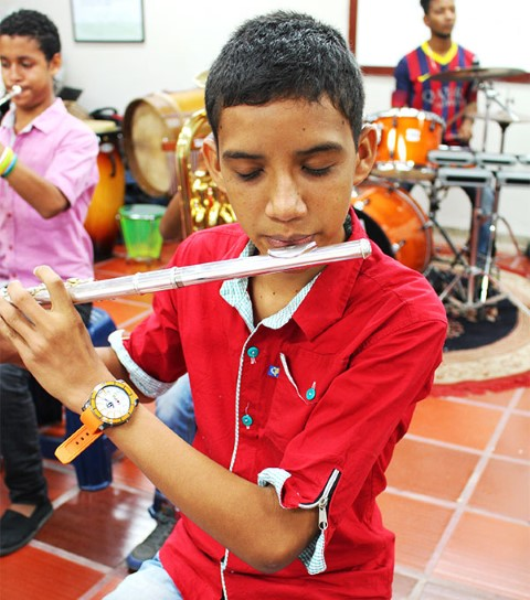 A boy practices the flute.