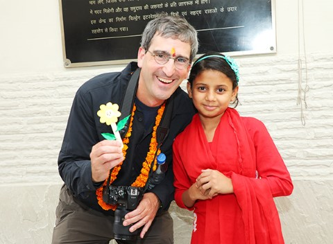 Children International supporter Laird Malamed and a child smile for a picture.