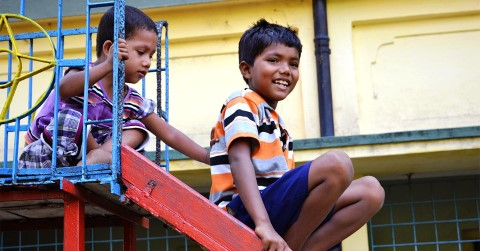 A little girl in Kolkata impatiently awaits her turn on the slide