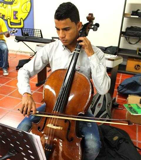 A young man practices the cello.