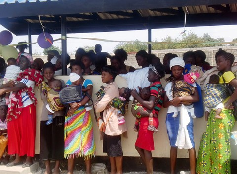 Lusaka mothers wait their turn at a health clinic under a shelter built by the CI Youth Council
