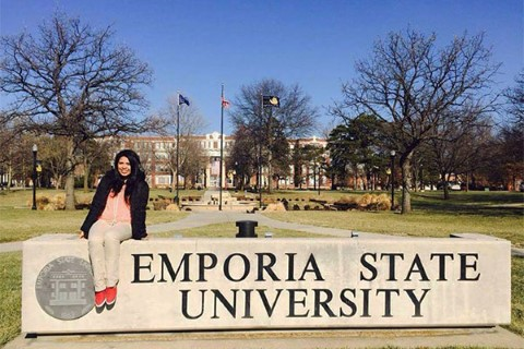 Johanny sits on the Emporia State University sign