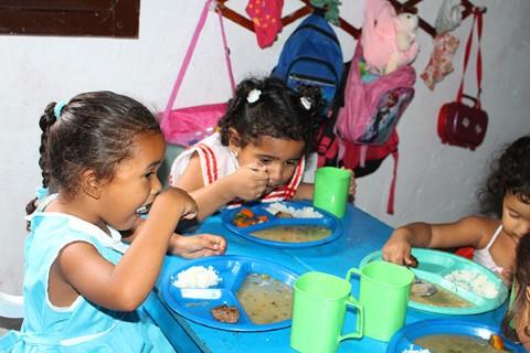 Niñas comen en una pequeña mesa durante el programa de alimentación.
