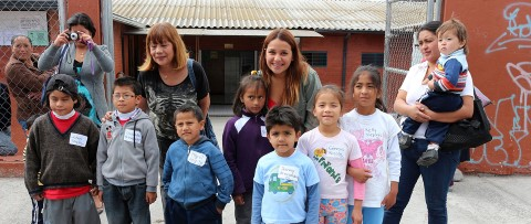 Sponsor and kids posing in front of community center.