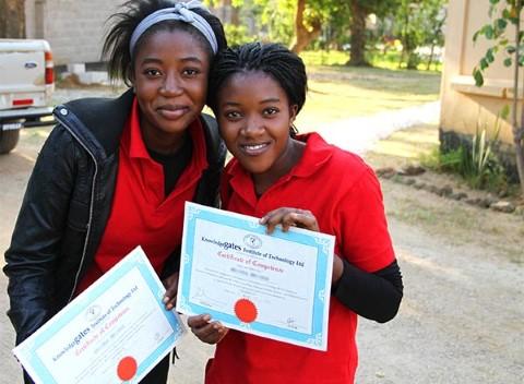 Hermanas demuestran sus certificados de informática.