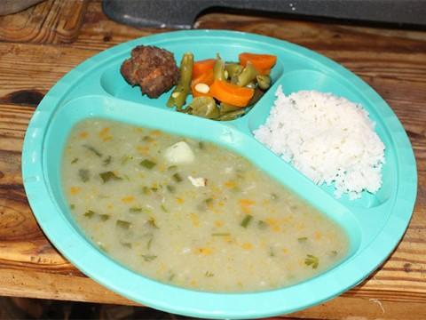 Albóndigas, verduras, arroz blanco y sopa de vegetales en un plato turquesa.