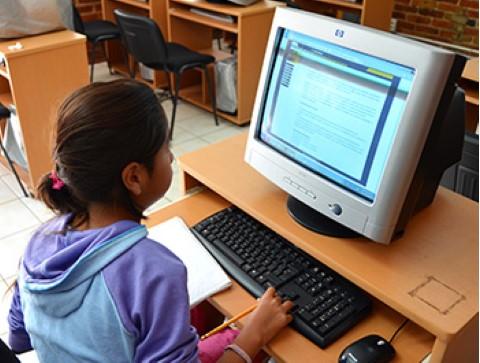 Una niña usa una sala de computación de Children International para leer un artículo en el internet.