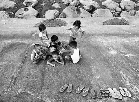 Siete niños juegan descalzos en el malecón inclinado a 45 grados.