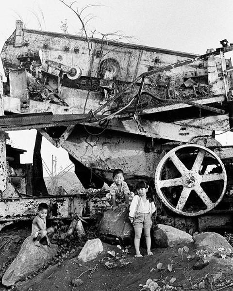 Tres niños juegan en una maquina grande oxidada.