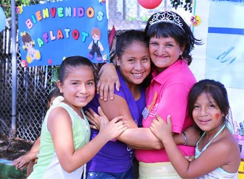 Una voluntaria abraza a niñas apadrinadas durante un evento en Guayaquil, Ecuador