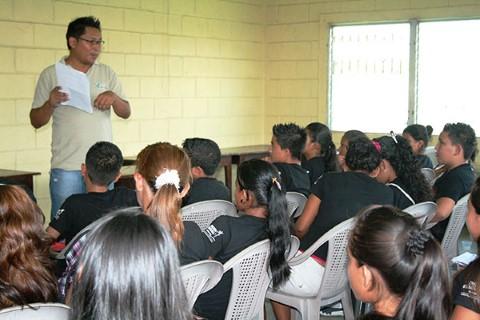 Un miembro del personal de Children International habla con un grupo de jóvenes en el centro comunitario