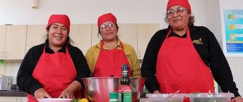 Volunteer mothers with CI's nutrition program in Ecuador stand in the kitchen with ingredients for salad.