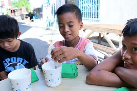 Un niño mezcla leche en una taza de Children International.