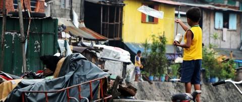 Boy flies a kite poor communitiy. Children International is helping solve Philippines poverty through child sponsorship.