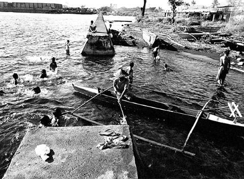 Un pescador navega por nadadores para atracar su lancha.