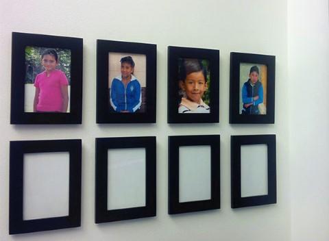 Fotos de los niños apadrinados colgadas en la oficina de Delos Advisors