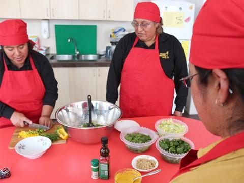 Mamás en Ecuador alistan los ingredientes para preparar una ensalada de quinua.