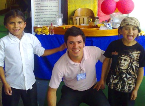 Carlos poses with two Ecuadorian kids at a food festival