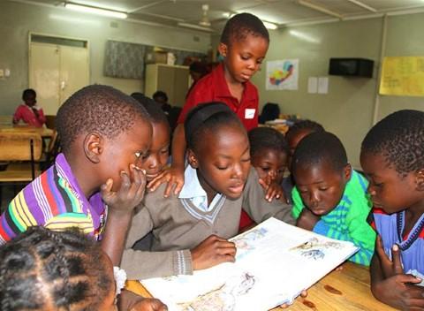 Una joven lee un libro a los niños en un centro comunitario de Lusaka