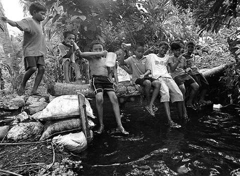 Niños pescan en un arroyo utilizando equipo improvisado.